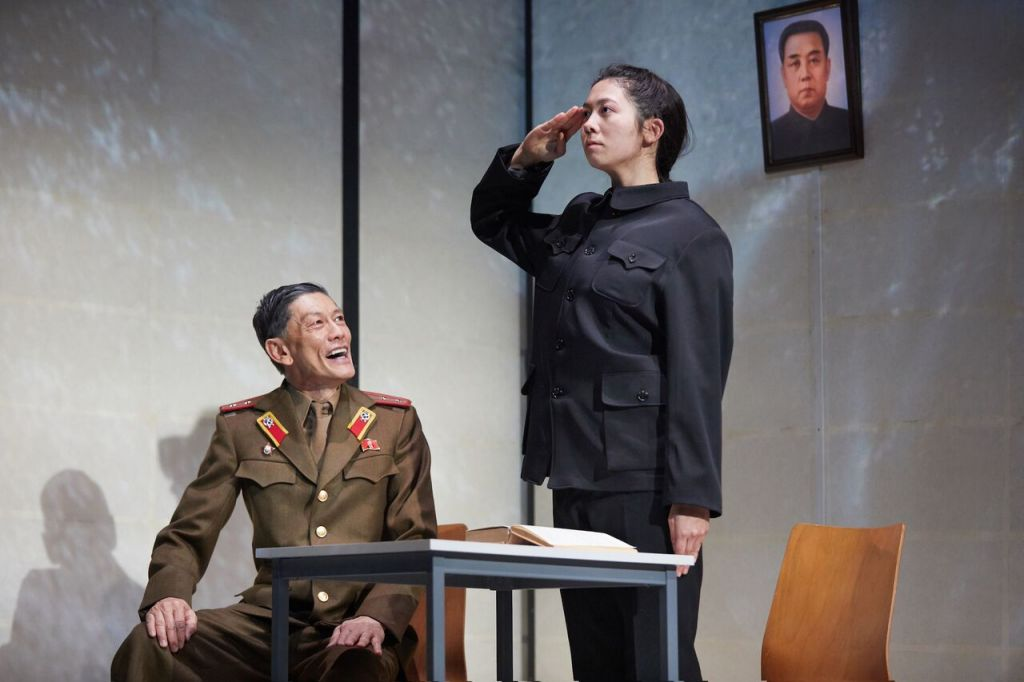 © Mark Douet, Kwong Loke (North Korean official) , Kirsty Rider (Hanako), abducted by North Korean commandos and being schooled in following the system...