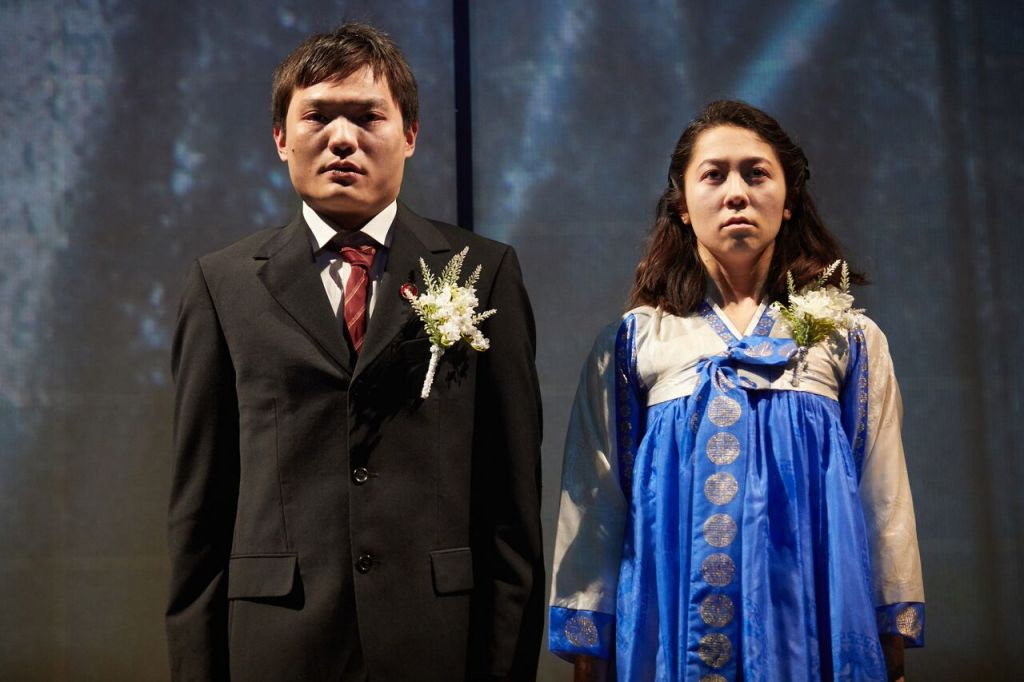 © Mark Douet, Vincent Lai as Kum-Choi and Kirsty Rider as Hanako - unhappy wife and husband pairing, serving the Great Leader by their marriage...