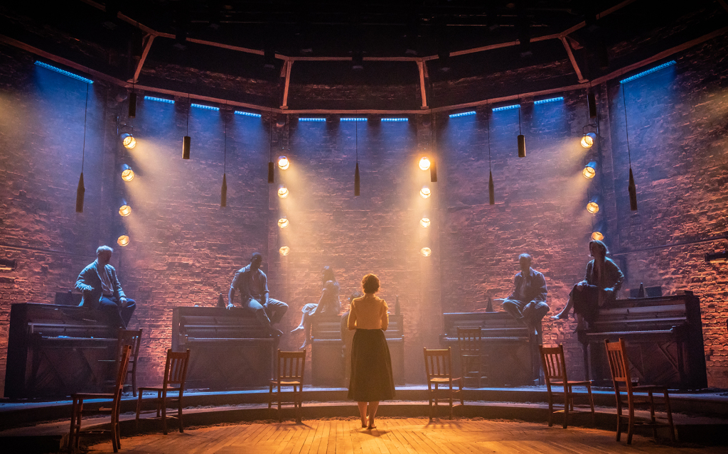 © Marc Brenner, Patsy Ferran carries the load as Alma in Rebecca Frenshall's superb revival. Here facing the chorus of pianos and the back brick wall distinctive of the Almeida auditorium and replicated in the West End setting.