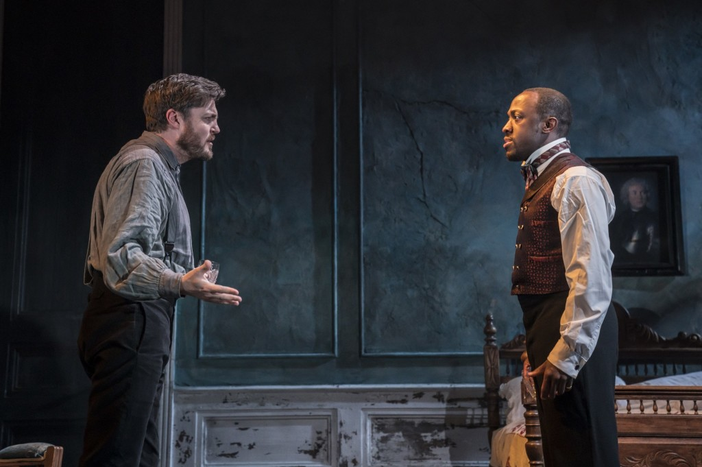 © Johan Persson, Tom Burke as Rosmer and Giles Terera as Governor Kroll aghast at Rosmer's change of heart, adoption of radical ideas, and loss of Christian faith...shock, horror...